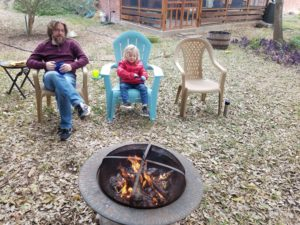 photo of eric and kiddo sitting around a campfire in the backyard.